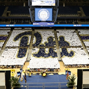 Pitt script logo created by class of 2016 members holding signs in Petersen Events Center