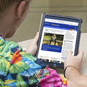 Male student reading Pittwire on a tablet