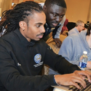 Stephen Canton in a black shirt types on a computer as another student sits next to him
