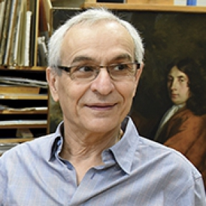Costas Karakatsanis headshot, wearing blue button down shirt with books/manuscripts and a painting in the background