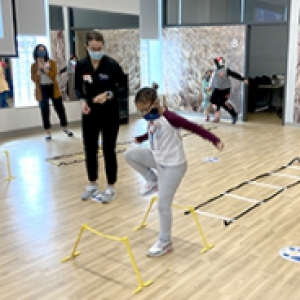 A child in a mask plays on an obstacle course as a SHRS mentor observes