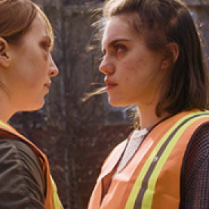 Two women in orange vests look at each other