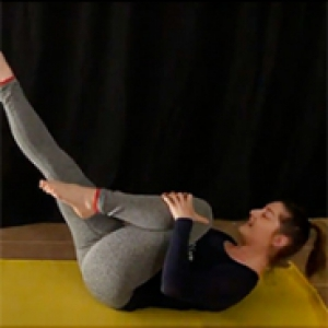 a woman on a yellow mat with legs in the air doing pilates