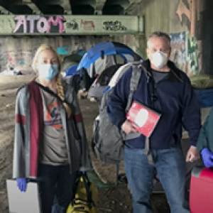 two people i masks carrying supplies standing under a graffitied area