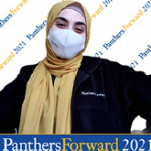 Woman in a yellow headscarf and a white mask with PanthersForward 2021 in the background
