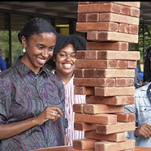Group of students standing at a table playing Jenga