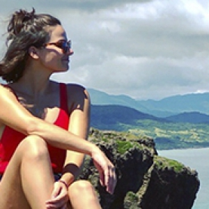 Juliette Rihl pictured seated in shorts and tank top in front of a view of mountains, water and cloudy sky