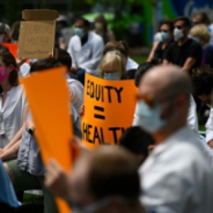 """People in masks holding up signs, one saying """"Equity = Health"""""""