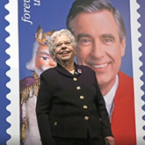 Joanne Rogers in front of a sign with Mister Rogers on it