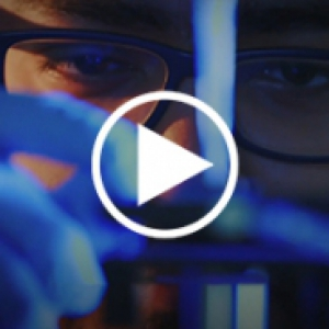 A person in glasses and blue gloves working with lab equipment