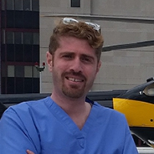 A man in blue scrubs standing by a helicopter