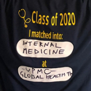 A person wearing a T-shirt that displays where they matched for residency