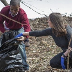 Two people put trash into bags outdoors