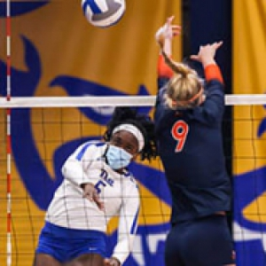 Four women play volleyball with a Pitt banner in the background