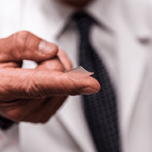 A person in a white coat and black tie holds a patch on their finger