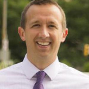 Chris Kline in a lavender shirt and purple tie