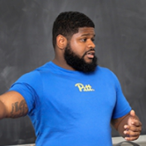 Christopher Darby in front of a blackboard, wearing a blue Pitt shirt