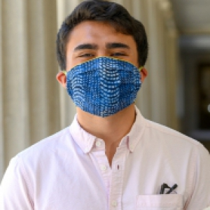 a person in a pinkish collar shirt and blue mask