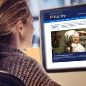 Woman looking at computer screen with Pittwire site displayed