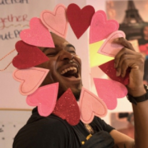 man smiling while holding up a wreath made of hearts around his face