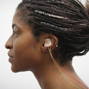 A earbud in a woman's left ear