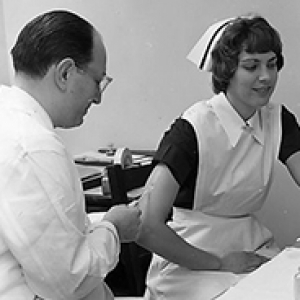 Salk administering a shot to a nurse
