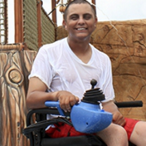 young man in a white shirt using a blue and black PneuChair