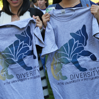 two people holding up gray t-shirts that say Year of Diversity